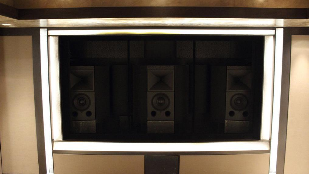 Speakers behind private home theater screen